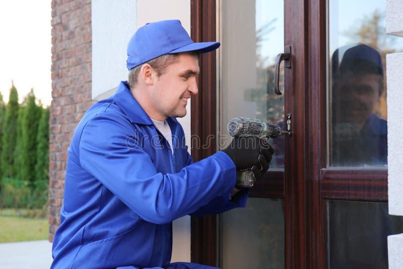 Pracownik budowlany naprawia szklanego drzwi zdjęcia royalty free