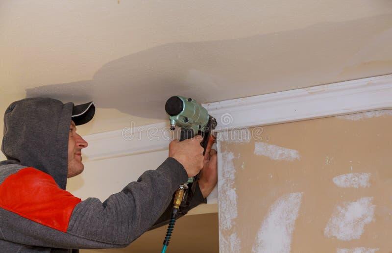 Pracownik budowlany przybijający w górę bagiety ściany w nowym domu obraz stock