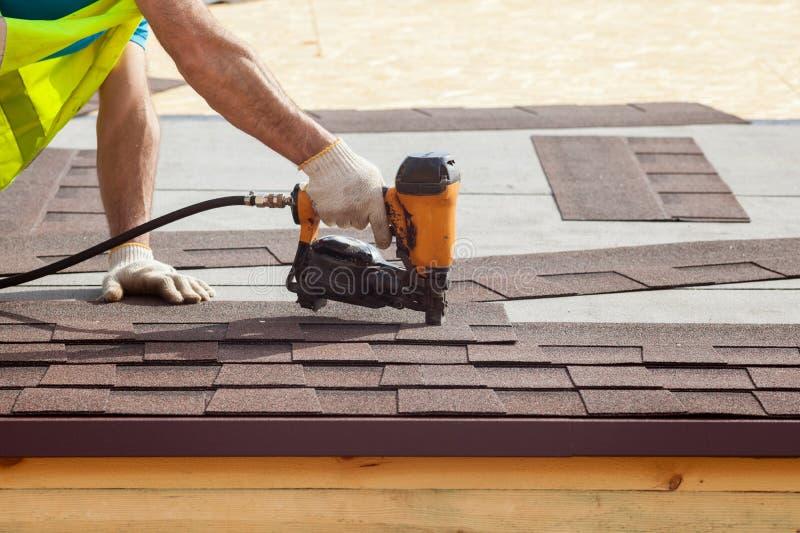 Pracownik budowlany stawia asfaltowego dekarstwa gonty z gwoździa pistoletem na nowym ramowym domu zdjęcie stock