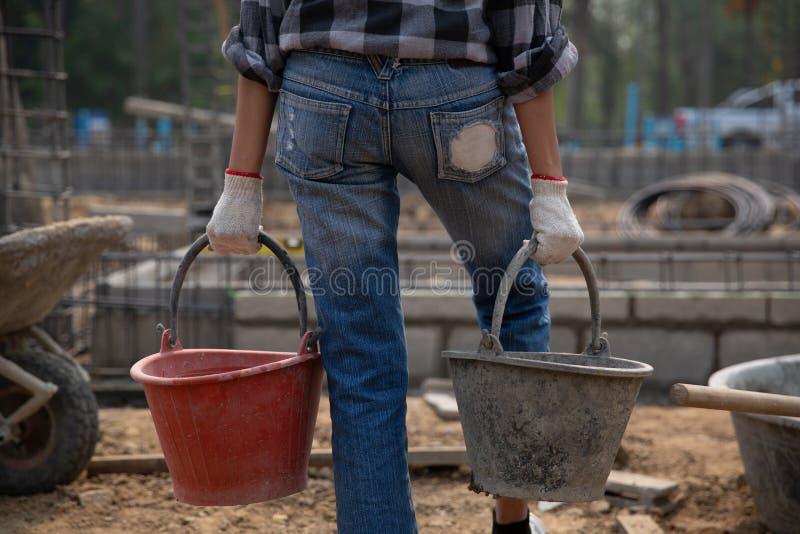 Pracownik budowlany trzyma wiadro mokry beton zdjęcie royalty free