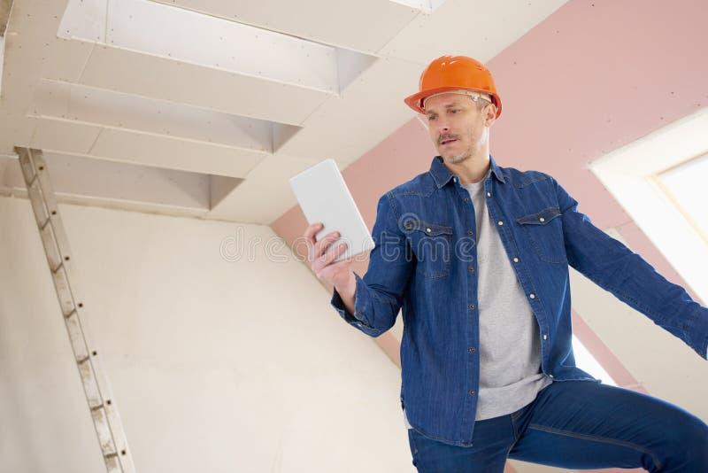 Pracownik budowlany używać cyfrową pastylkę zdjęcie stock