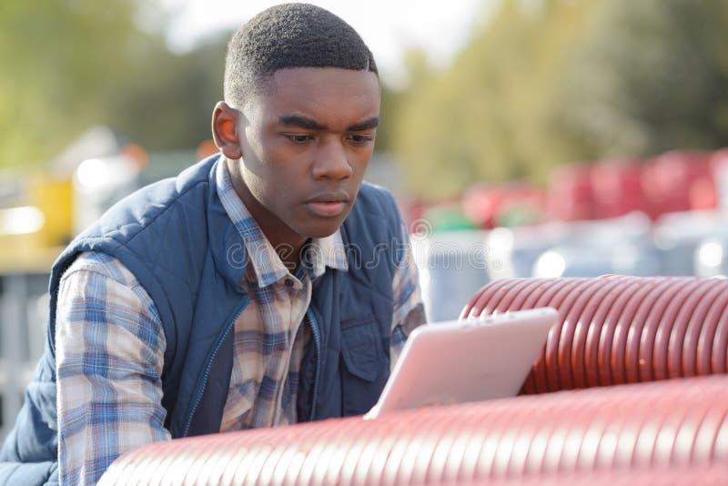 Pracownik budowlany używa pastylkę obok drymb outdoors obraz stock
