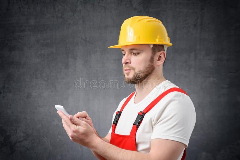 Pracownik budowlany u?ywa smartphone obrazy royalty free