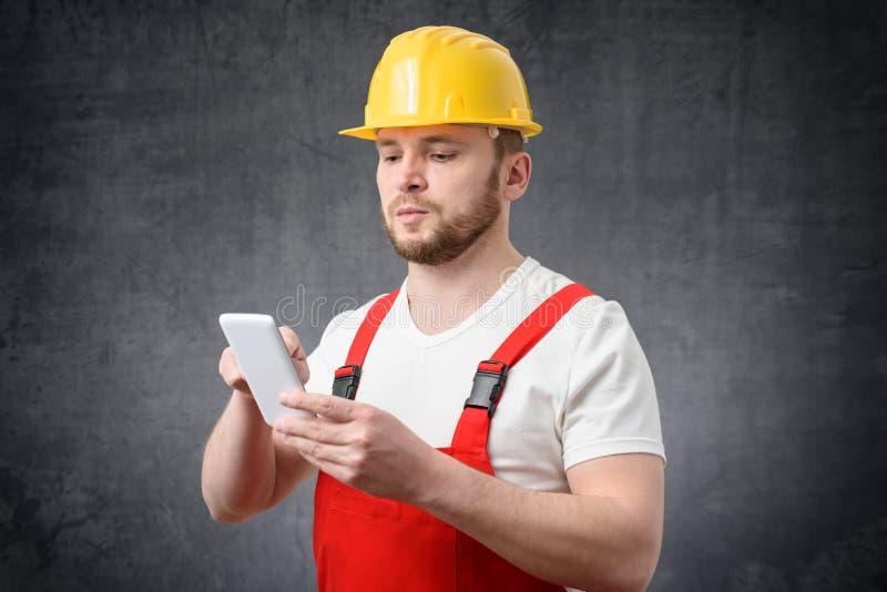 Pracownik budowlany u?ywa smartphone obrazy stock