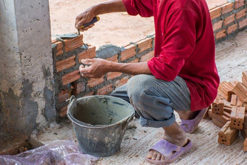 Pracownik budowlany umieszcza cegły na cemencie dla budować exteri obrazy stock