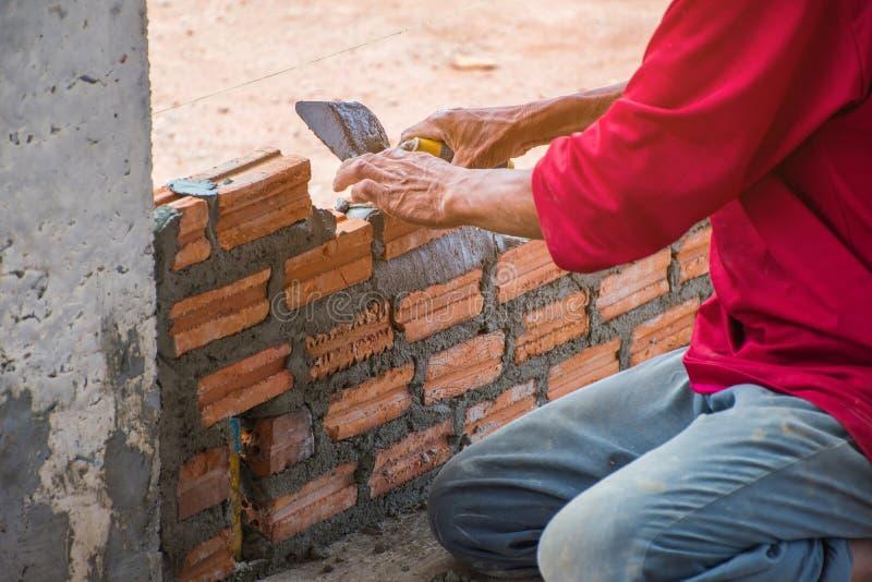 Pracownik budowlany umieszcza cegły na cemencie dla budować exteri obraz stock