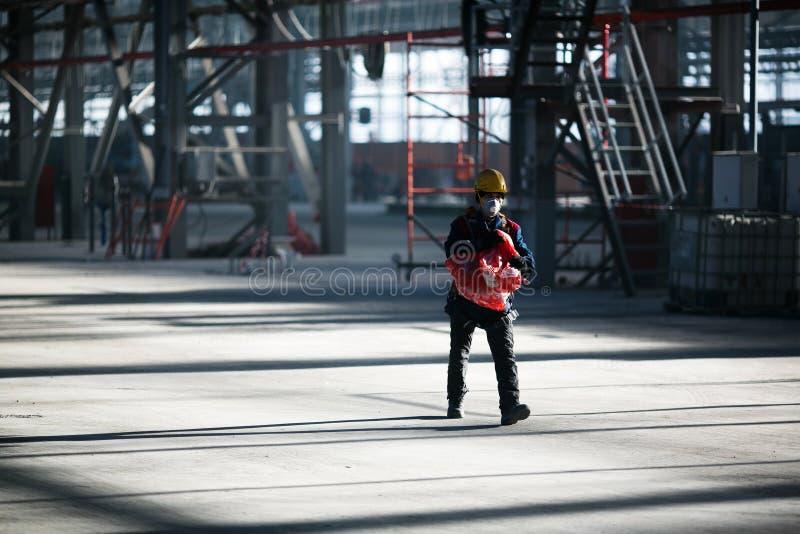 Pracownik budowlany w kontuszu chodzi wzdłuż produkcja warsztata stoczniowy wsad Zvezda obrazy royalty free