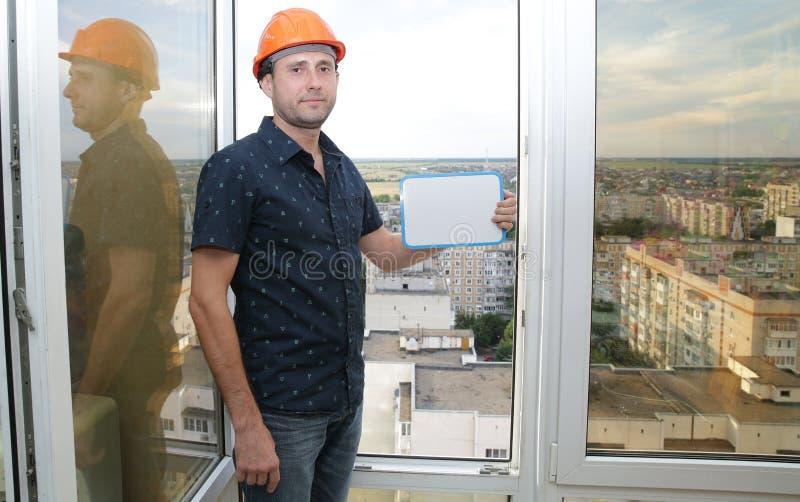 Pracownik budowlany w ochronnym hełmie z pastylką dla pisać w ręce z kopii przestrzenią przed otwartym okno na wysokości obraz stock