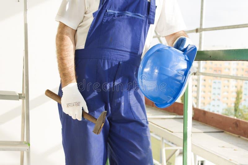 Pracownik budowlany w praca ubiorze, ochronne rękawiczki trzyma hełm i młot Praca przy dużą wysokością Rusztować w zdjęcia royalty free