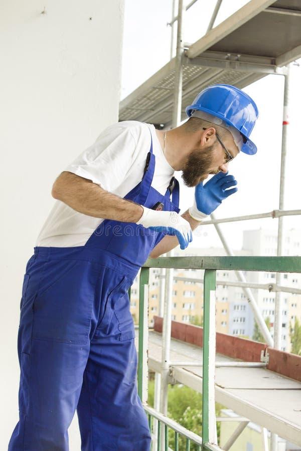 Pracownik budowlany w pracującym stroju w ochronnych hełmów stojakach przy dużą wysokością na budowie i zdjęcie stock