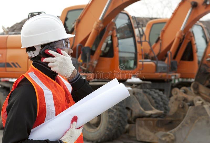 Pracownik budowlany z budynku telefon komórkowy i planami zdjęcia royalty free