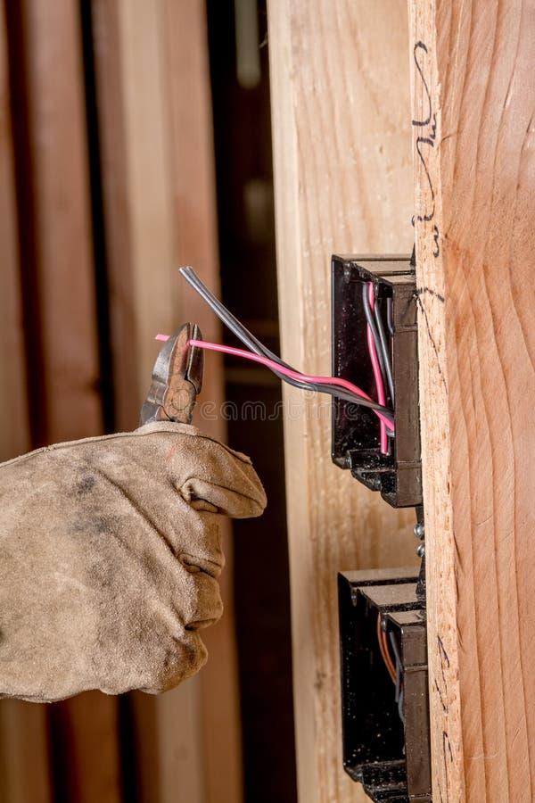 Pracownik budowlany z rękawiczką używa drucianych nippers ciąć elektrycznego drut obrazy stock