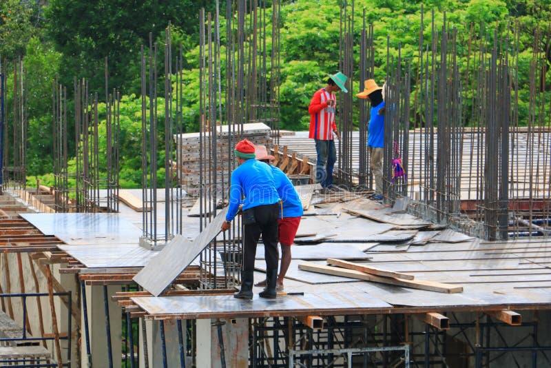 Pracownik budowy drużyna pracuje na wyższość budynku reklamie w miejsca miejscu pracy obraz stock