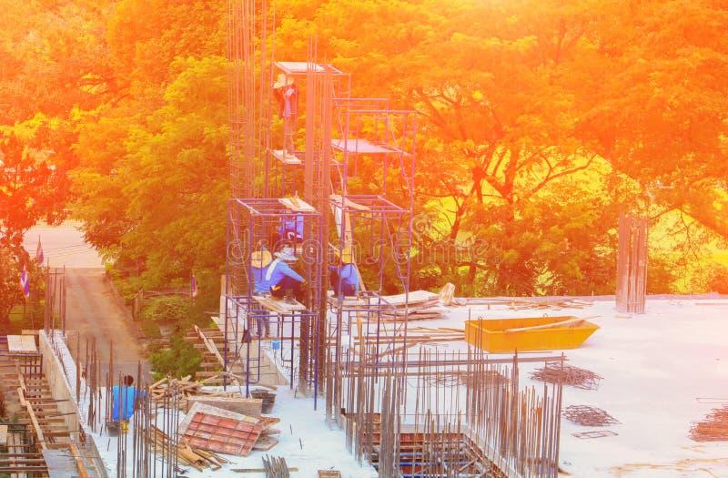 Pracownik budowy drużyna pracuje na wyższość budynku reklamie w miejsca miejscu pracy z wschodu słońca światłem zdjęcia royalty free