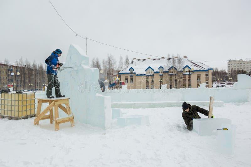 Pracownik ciie gomółki lód z piłą łańcuchową zdjęcie stock