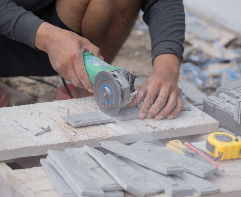 Pracownik ciie piaska kamienia płytkę używać kąta ostrzarza obraz stock