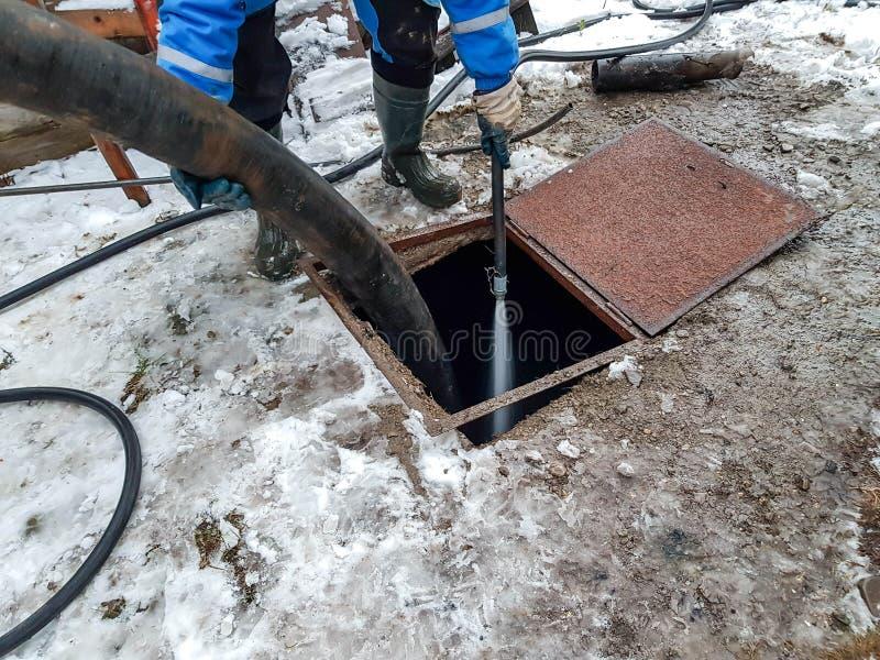 Pracownik czyści septycznego zbiornika z wodą po opróżniać kanalizacyjną czystą maszynerią obrazy royalty free