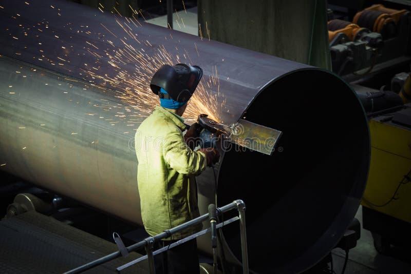 Pracownik czyści spawającego szew na stalowej drymbie używać szlifierską maszynę w metalwork warsztacie fotografia stock