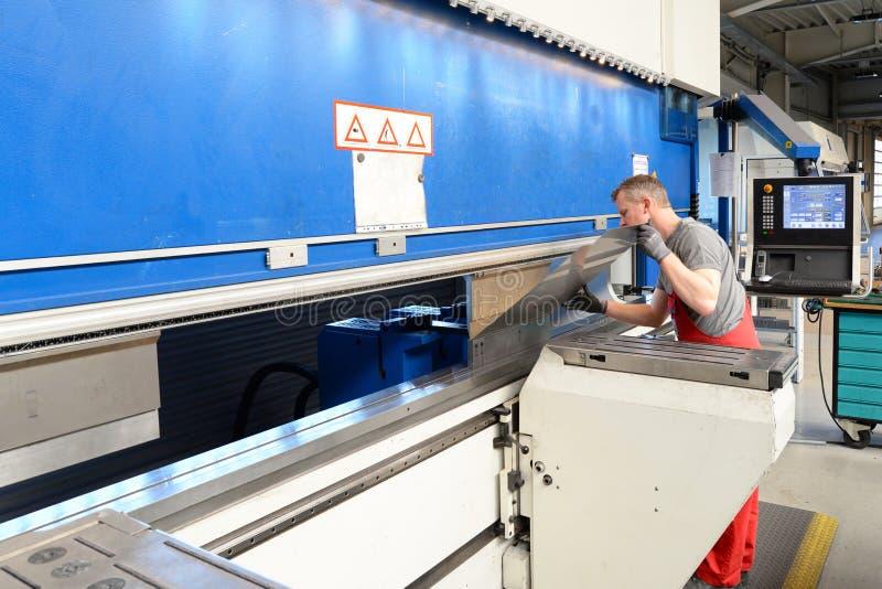 Pracownik działa chylenie maszynę w metalworking firmie - chylenie szkotowy metal dla dalszy przerobu zdjęcie stock