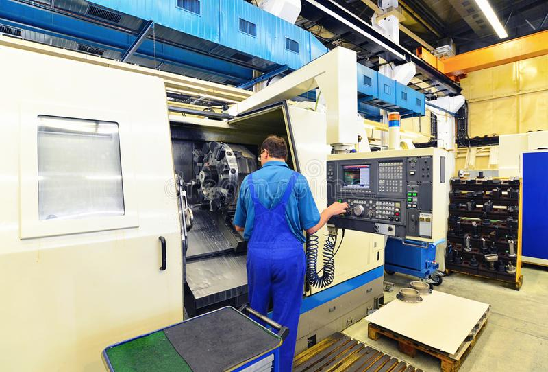 Pracownik fabryczny działa cnc mielenia maszynę dla produkci obrazy royalty free