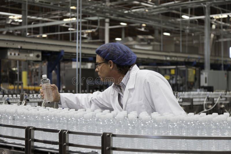 Pracownik fabryczny egzamininuje wodę butelkową obraz royalty free