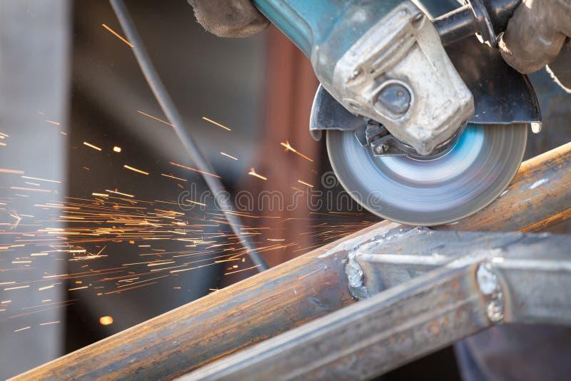 Pracownik fabryczny używa elektrycznego ostrzarza maszynowego rozcięcia metal błyska obrazy stock