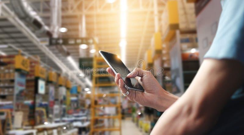 Pracownik fabryczny używa zastosowanie na mobilnym smartphone działającym fotografia royalty free