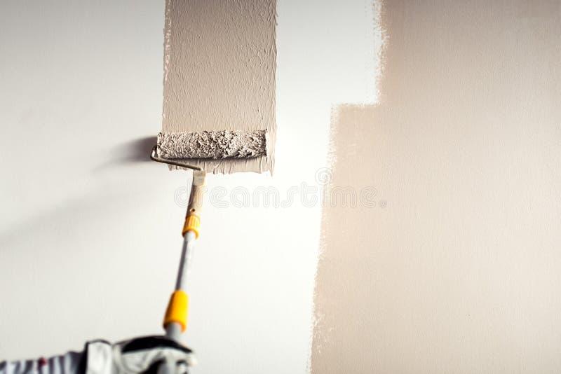 Pracownik gipsuje ścianę, maluje z farby muśnięcia dekoracją na wewnętrznych ścianach zdjęcie stock