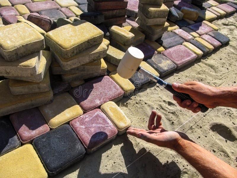Pracownik instaluje bruk płytek ` Stary Grodzki ` zdjęcia stock