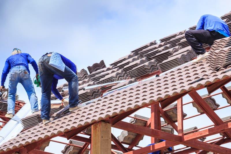 Pracownik instaluje dachową płytkę dla nowego domu obrazy royalty free