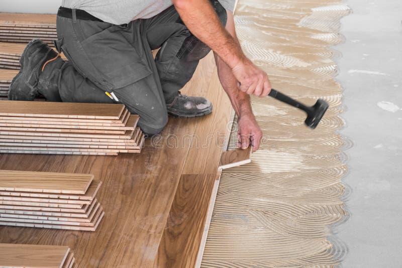 Pracownik instaluje drewniane podłoga deski obrazy stock