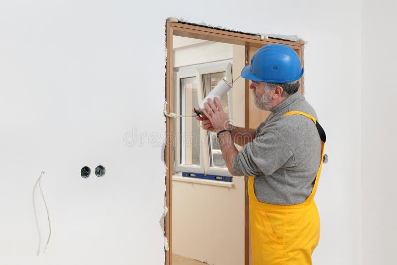 Pracownik instaluje drewnianego drzwi, używać polyurethane pianę obrazy royalty free