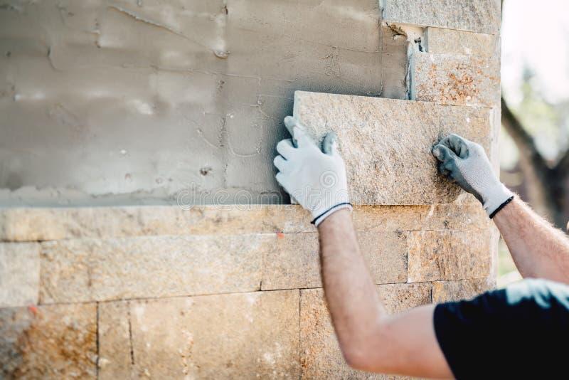 Pracownik instaluje kamień na architektonicznej fasadzie nowy budynek Szczegóły przemysł budowlany obraz royalty free