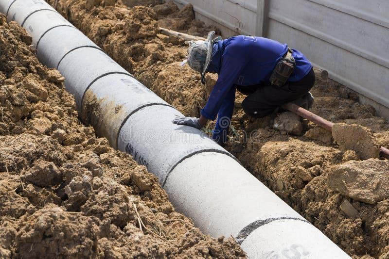 Pracownik instaluje Precast betonu manholes obraz royalty free