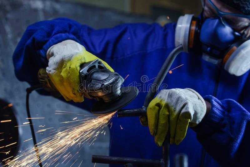 Pracownik jest ubranym ochrony wyposażenie używać kąta ostrzarza na metalu obrazy stock