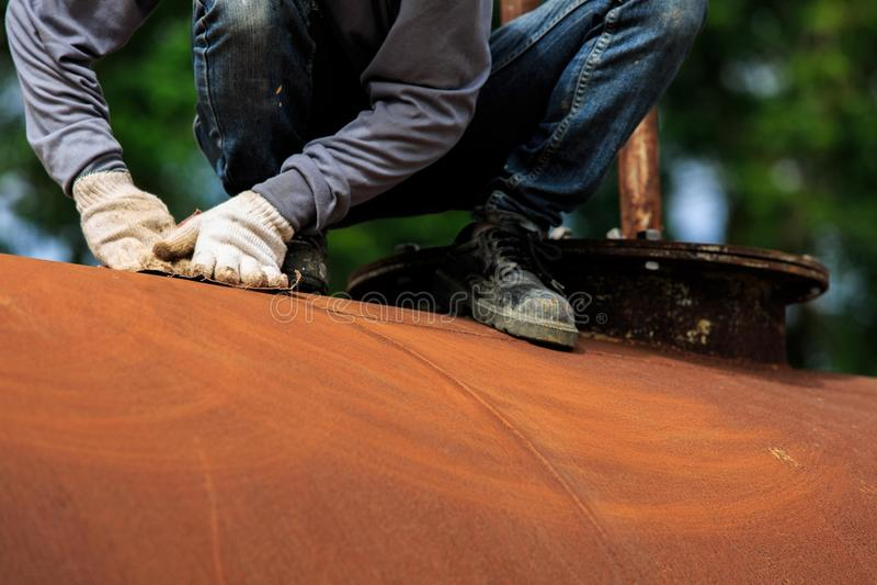 Pracownik jest usuwa farbę piaska papierem obraz stock
