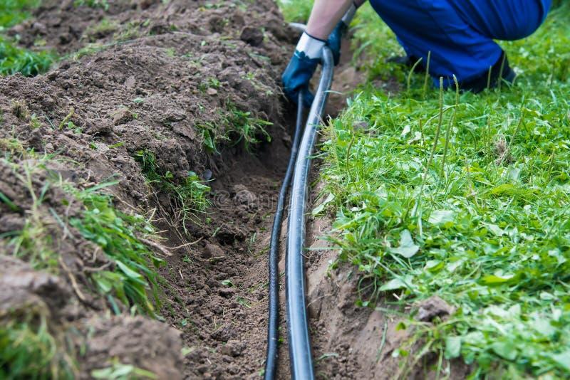 Pracownik kłaść wodną drymbę w ziemię zdjęcia stock