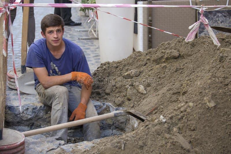 Pracownik kopał jamę dla remontowej pracy z wodną drymbą Naprawy i zastępstwa ściekowe drymby podczas dnia przy dnem głęboki okop zdjęcia stock