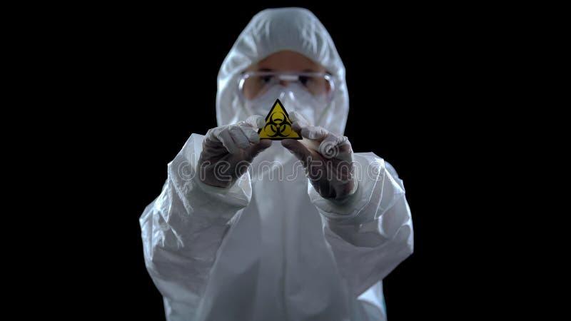 Pracownik laboratorium w garniturze ochronnym z symbolem zagrożenia biologicznego, broń zdjęcia royalty free