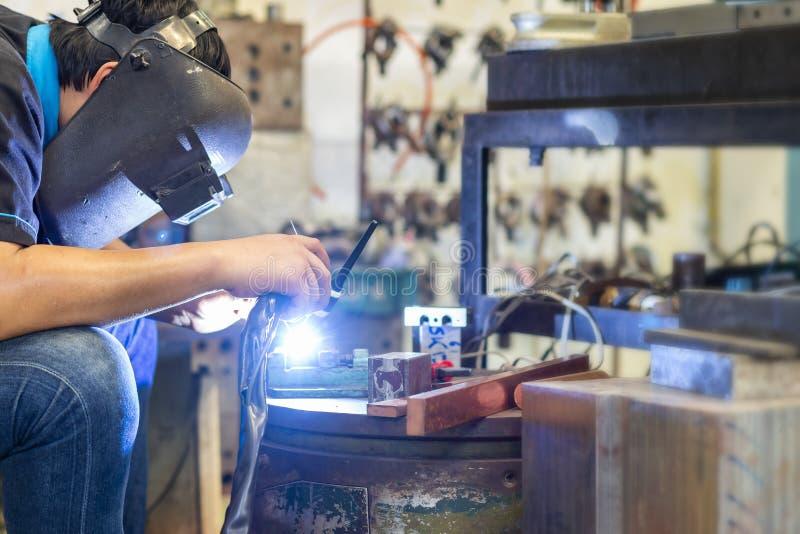 Pracownik lub spawacz jest ubranym podczas spawalniczej metal części przy fabryką maskę dla, workpiece lub błyskotanie jaskrawego obraz stock