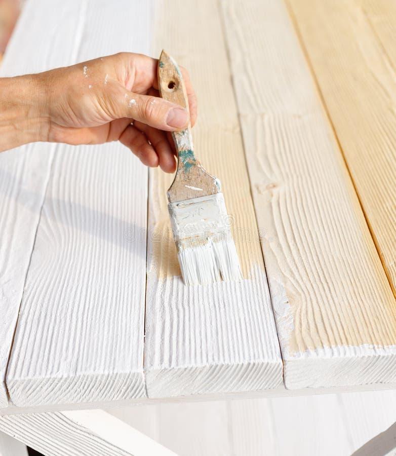 Pracownik maluje biały drewniany meblarski plenerowego fotografia royalty free