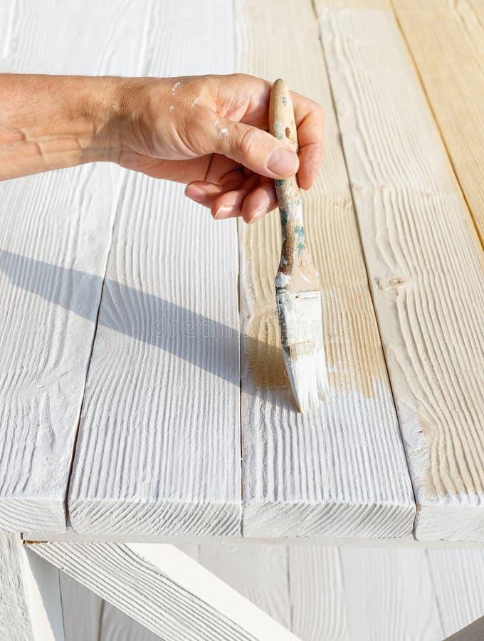 Pracownik maluje biały drewniany meblarski plenerowego obraz stock