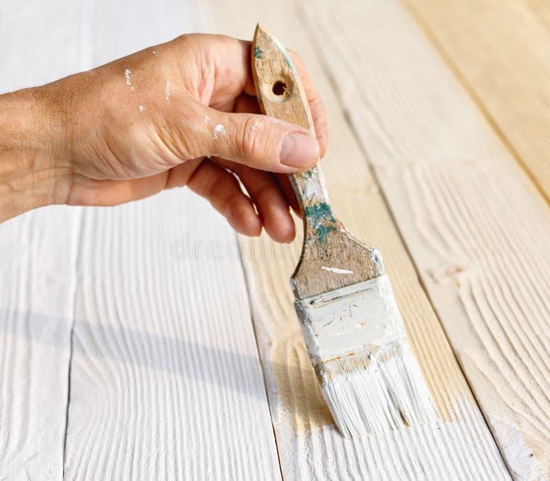 Pracownik maluje biały drewniany meblarski plenerowego zdjęcia royalty free