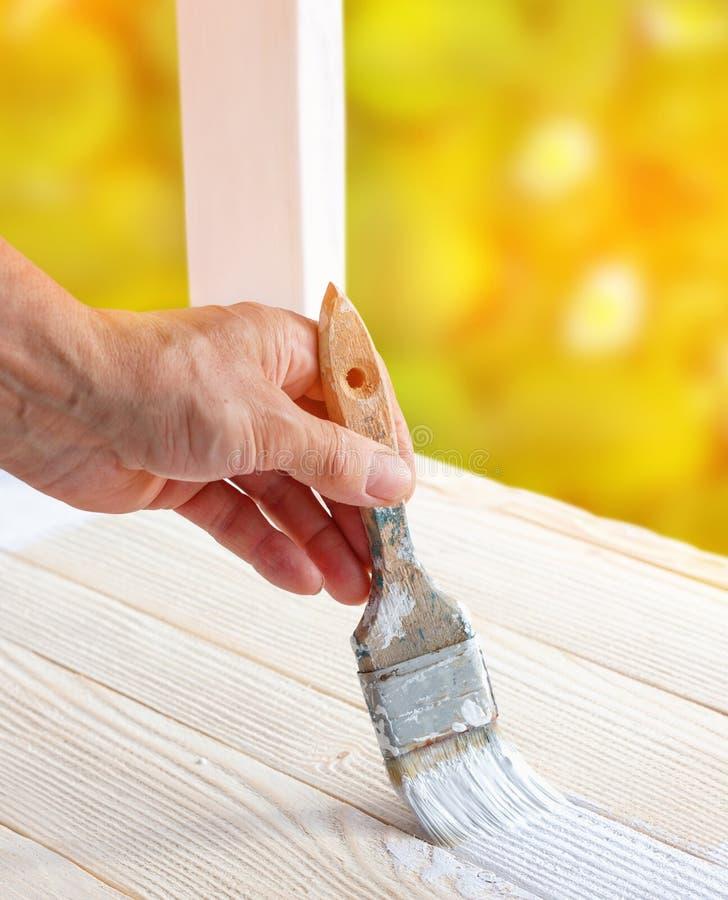 Pracownik maluje biały drewniany meblarski plenerowego zdjęcia stock