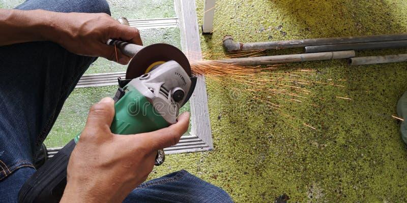 Pracownik mleje stalowej drymby ostrzenie, ręk stalowi strzyżenia używać maszynę zdjęcie royalty free