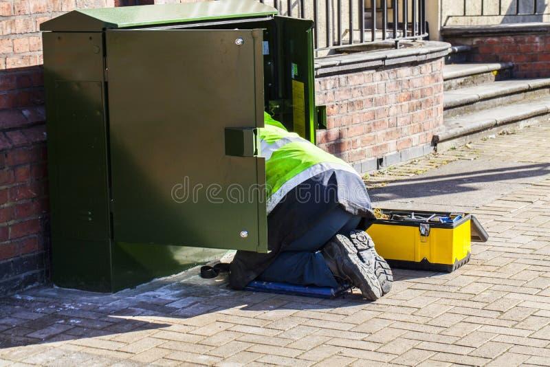Pracownik na ulicznym działaniu w elektryczności pudełku Ochrona na praca konceptualnym wizerunku Mężczyzna na kolanach pracuje n zdjęcie royalty free