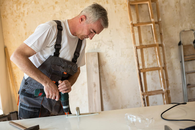 Pracownik naprawia drzwi w cieśli ` s warsztacie obraz royalty free