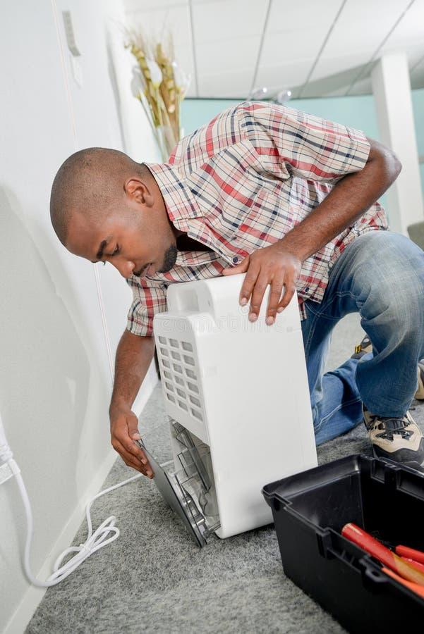 Pracownik naprawia urządzenie obrazy stock