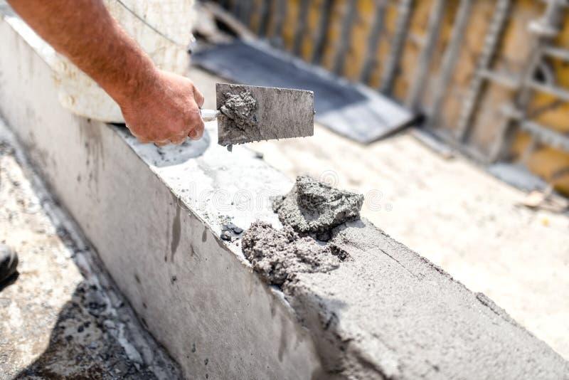 Pracownik niwelaci beton z kitu nożem przy placem budowy Szczegóły przemysł budowlany obraz royalty free