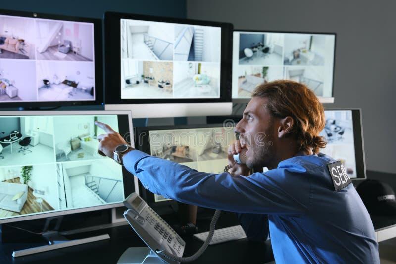 Pracownik ochrony monitoruje nowożytne CCTV kamery w inwigilacja pokoju fotografia stock